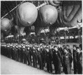 Balloons safely tucked away in the hangar for the night. W.A.A.F. balloon operators report for inspection before... - NARA - 541911.tif