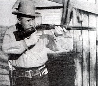 "Bill Tilghman - Bill Tilghman posing with his Winchester rifle in a scene from 1915 movie ""The Passing of the Oklahoma Outlaws"""