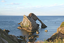 A large brown rock with a striking shape lies just beyond a rock coast in a blue sea under a pale blue sky. The left hand and foreground part of the rock is wedge shaped and the sedimentary rocks it is made off are set at a 45 degree angle to the horizontal. A second part of the rock is in the shape of an arch with a thick top section and a thin downward leg. The whole structure has a strangely contrived air, suggestive of a wrecked ship.