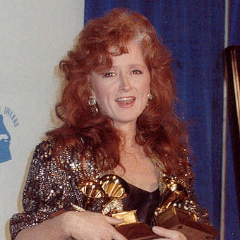 A woman with curly red hair wearing a sparkling jacket and holding three gold trophies.