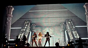 A female blond performer standing with two dancers in front of two giant LED screens, which has an image of a pyramid.