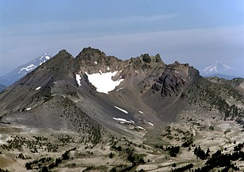 A highly eroded volcano with jagged cliffs, with two steep volcanoes in the background to its left and to its right.