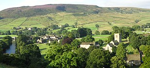 Village of Burnsall, from east above, showing bridge, Wharfe, chapel, Dalesway path (2008)