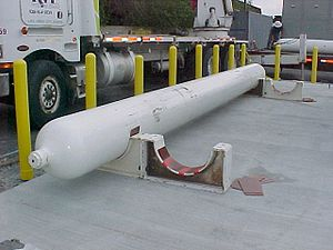 Micarta - Compressed natural gas storage cylinder in the process of being installed in saddle supports using micarta insulation as an electrical insulator.