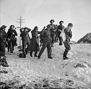 four Germans one with a white g=flag surrounded by British troops crossing a snow covered landscape