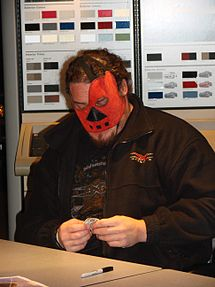 Large adult male wearing a black shirt and jacket, as well as a red mask over his face with shirt brown hair.