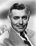 Black and white promo photo of Clark Gable in 1940--a middle-aged white man with mustache and straight gray hair combed to the side, wearing a suit and smiling.