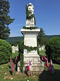 A stone Confederate monument decorated in an evergreen garland and surrounded by Confederate flags implanted in the ground beneath it.