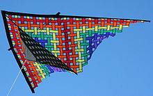 A colorful triangular kite against a blue sky