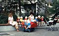 East Berlin childminders, with children and strollers, seated on a wall, 1984.jpg