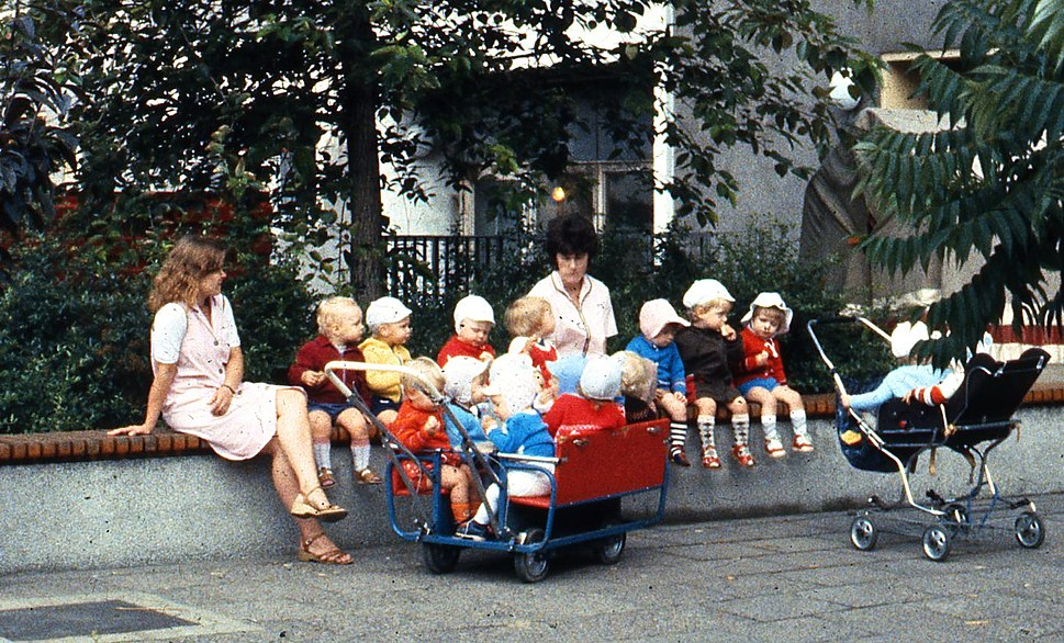 East Berlin childminders, with children and strollers, seated on a wall, 1984