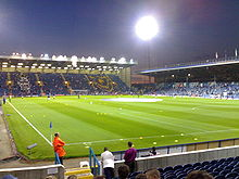 Fratton Park football stadium at night, home to Portsmouth F.C. The pitch is lit by floodlights.