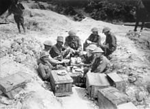 Eight men, most wearing steel helmets, sit in a shell hole surrounded by wooden crates.