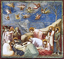 Square fresco. In a shallow space like a stage set, lifelike figures gather around the dead body of Jesus. All are mourning. Mary Magdalene weeps over his feet. A male disciple throws out his arms in despair. Joseph of Arimethea holds the shroud. In Heaven, small angels are shrieking and tearing their hair.