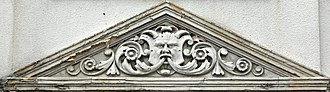 Harringay - Tympanum style ornamentation with a bas-relief green man decoration on one of the Grand Parade Buildings