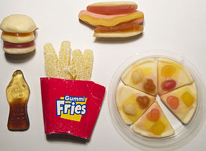 Gummi candy - A cola bottle gummi candy, alongside a gummi hot dog, pizza, hamburger, and box of fries.
