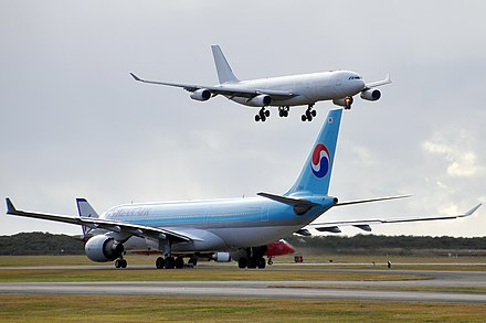Compared to the A330 twinjet (on ground), the heavier A340 (inflight) has four engines and a centre-line wheel bogie HL7552 Airbus A330-223 Korean Air, CS-TQM Airbus A340-313X Strategic Airlines (HiFly) and VH-ZPL 'Samba Blue' Embraer 190-100IGW Virgin Blue (Virgin Australia) (6600549415).jpg