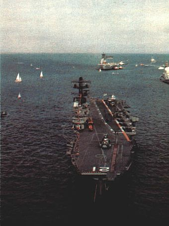 Colour photo of a small aircraft carrier, taken from an elevated position. The carrier is sitting bow on, with one of her anchor chains deployed.