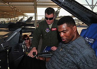 56th Training Squadron - Major Matt Busch of the 56th Training Squadron explains the controls of an F-16 Fighting Falcon to Herschel Walker at Luke AFB