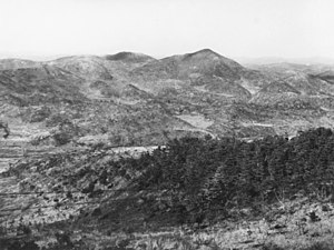 Seria ridgelines i strome wzgórza w oddali, z Maryang Sanu po prawej stronie.  Na pierwszym planie jest mocno roślinnością pagórek, w dolinie w ziemi interwencyjnym.