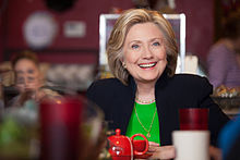 Hillary Clinton dressed in a black suit and a green shirt, sitting in a café. She is smiling, and a red teacup is situated in front of her, the foreground is distorted due to the presence of various small objects.