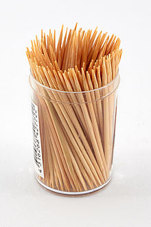 Photograph of a container full of wooden toothpicks.