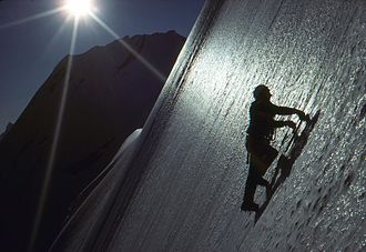 Extreme sport - A free solo ice climber on a steep ice slope, with personal safety gear (such as a helmet) but completely without a rope or any form of protection from fall