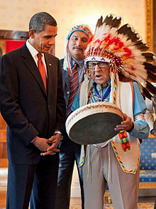 An old man in full feathered headdress plays a drum with a man in a suit watching