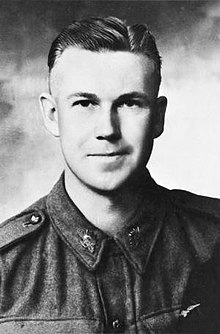 "Head and shoulders of a man with short, dark hair. His tunic is buttoned at the collar and he wears Australian Army ""rising sun"" badges."