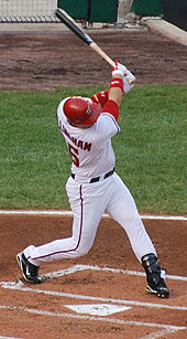 A man, clutching a baseball bat and wearing a red batting helmet and a white baseball uniform with his surname and number partially obscured on his back, swings at a pitch.