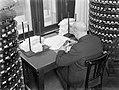 Kantoorbediende stempelt documenten. Naast hem stempelstandaards, Bestanddeelnr 189-0012.jpg