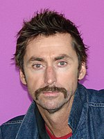 A man with brown hair and a brown mustache wearing a blue denim jacket looks directly ahead.