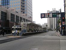 A train station in the middle of a street. A light rail train is stopped on the far track.