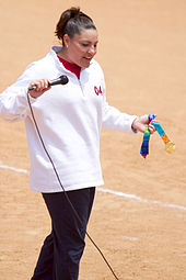 A standing brunette woman, wearing a white sweatshirt, holding a microphone in her right hand and a gold medal in her left.
