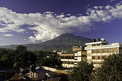Mount Meru in the background of the city of Arusha during the day time.