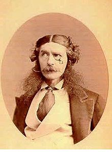 Head and shoulders portrait of a foppish Victorian gentleman wearing a monocle, with longish hair parted in the middle and curly at each side, exaggerated long bushy sideburns and a handlebar moustache. He wears a jacket with very wide lapels, an upright collar and wide tie tucked into his double breasted waistcoat.