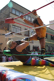A Mexican wrestler placing his foot on the throat of a seated opponent.