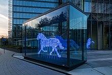 Fotografia de uma escultura de um cavalo trotando.  A escultura foi feita usando uma série de faixas horizontais.  Cada banda é feita a partir de um tubo de vidro que brilha em azul.  As bandas são empilhados para indicar a forma de um cavalo;  a separação entre as bandas tem aproximadamente a mesma largura que a tubagem de vidro.  A escultura é dentro de uma caixa de vidro grande que foi colocado na praça entre alguns edifícios de escritórios.