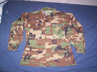 "Battle Dress Uniform - U.S. Marine Corps BDU blouse in woodland pattern, wearer's nametape removed. The ironed-on ""EGA"" on the breast pocket is barely visible due to wear."