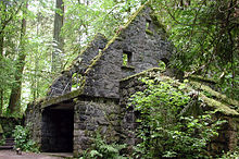 Ruins of a moss-draped stone building rest near a path in a thick forest.
