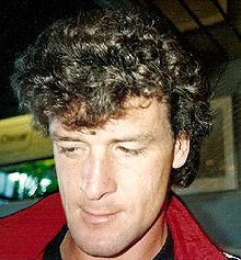 A head shot of a young man with curly long brown hair that is greying slightly. He is looking down, away from the camera and the red collar of a jacket is visible.