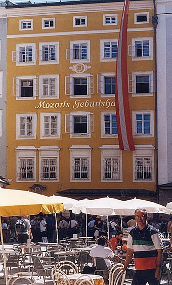 "The Mozart family's house, No. 9 Getreidegasse, Salzburg, photographed in 1998. The family's quarters were on the floor immediately above the sign ""Mozarts Geburtshaus"". Mozart.birth.500pix.jpg"