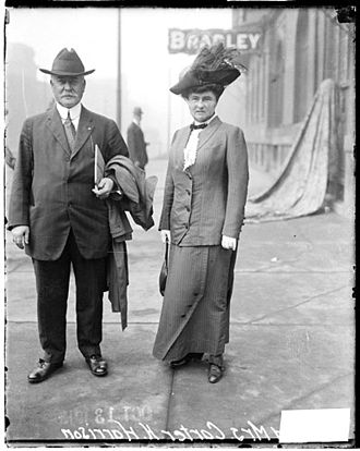 Carter Harrison Jr. - Chicago Mayor Mr. and Mrs. Carter Harrison Jr. on a sidewalk (likely near North Rush Street and East Grand Avenue, 1913)
