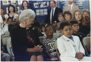 Barbara Bush and a young girl, seated next to each other in a room full of people and smiling at each other