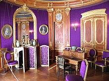 salle ronde aux murs couverts de violet et de boiseries dorées avec miroirs et portraits au pastel. La salle comprend un secrétaire au centre, un paravent et des chaises tapissés de violet