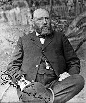Łysiejący mężczyzna z dużą brodą, ubrany w ciemny garnitur