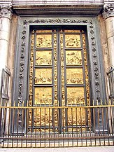 A pair of large bronze doors, with ornate frames. The doors are divided into ten rectangular sections with decorations between them, each section contains a relief sculpture telling a story from the Old Testament. The panels and parts of the frames are covered with gold.