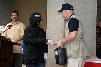 Informant - A representative from the U.S. State Department congratulates and offers a partial payment to a fully disguised informant, whose information led to the neutralization of a terrorist in the Philippines.