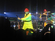 In the middle of a stage, a man wearing a yellow suit and a red hat plays a guitar. In the background is a similarly dressed man playing drums. A crowd is visible in the foreground.