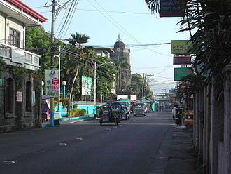 Santa Cruz, Laguna - Pedro Guevara Avenue. At left is the Spanish-era Escuela Pía building. The bell tower of the Church of the Immaculate Conception can be seen at the background.